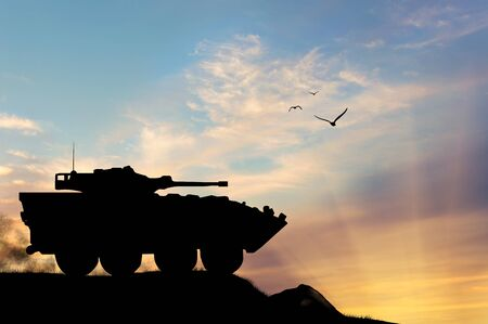 oncept: ?oncept of war. Silhouette military APCs at sunset