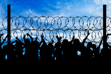 illegals: Concept of security. Silhouette of refugees climb over the barbed wire at the border