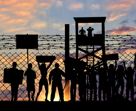 illegals: Concept of security. Silhouette refugees protesting outside the metal fence with barbed wire on the background of night sky