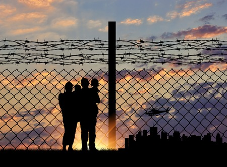 Silhouette of a family with children of refugees and fence with barbed wire on the background of evening city away