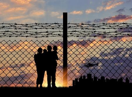 Silhouet van een gezin met kinderen van vluchtelingen en hek met prikkeldraad op de achtergrond van de avond stad weg