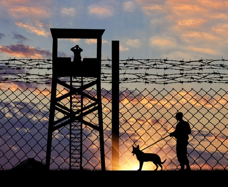 Concept of security. Silhouette of a lookout tower and a guard with a dog on the background of the fence with barbed wire at sunset Stockfoto