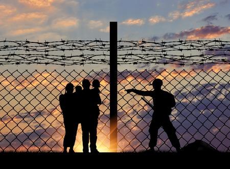 El concepto de seguridad. Silueta de una familia con niños de los refugiados y los guardias de fronteras y una cerca con alambre de púas en el fondo de la ciudad de noche lejos