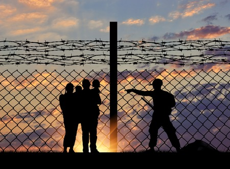 The concept of security. Silhouette of a family with children of refugees and border guards and a fence with barbed wire on the background of evening city away