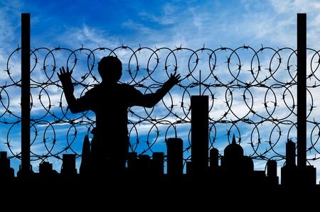 illegals: Safety concept. Silhouette of a refugee near the fence of barbed wire on the background of the city away