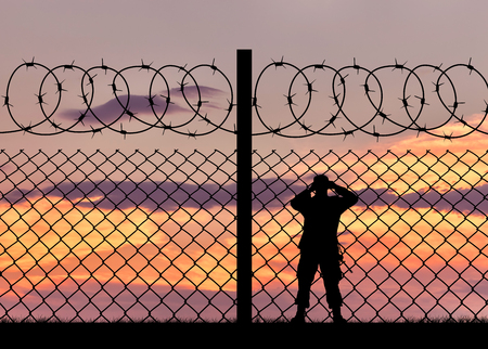 Concept of security. Silhouette of a military border guard and a fence on the background of sunset 免版税图像