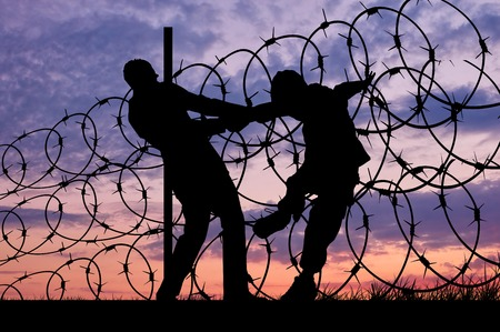 middle east war: Concept of security. Silhouette of refugees climb over the barbed wire at the border