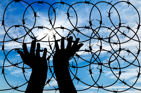 barb wire: concept of the refugees. Silhouette of a hand outstretched to the sun in the sky background barbed wire Stock Photo