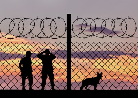 middle east crisis: Concept of security. Silhouette of the military with a dog on the background of the fence with barbed wire at sunset