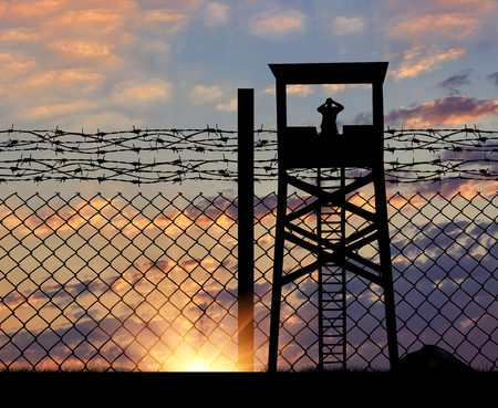 illegals: The concept of security. Silhouette of the observation tower on the background of the fence with barbed wire at sunset Stock Photo