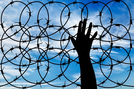 illegals: concept of the refugees. Silhouette of a hand outstretched to the sun in the sky background barbed wire Stock Photo