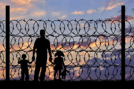 Concept of security. Silhouette of refugee men and metal fence with barbed wire on the background of night sky