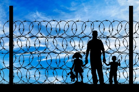 Silhouette of a family with children of refugees and fence with barbed wire on the background of the beautiful sky Archivio Fotografico