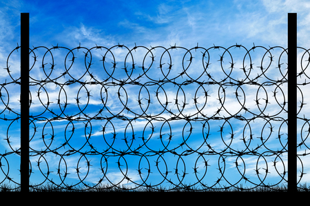 ancient prison: Concept of security. Silhouette of a metal fence with barbed wire on the background of the beautiful sky Stock Photo