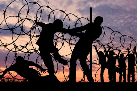 refugees: Concept of security. Silhouette of refugees climb over the barbed wire at the border