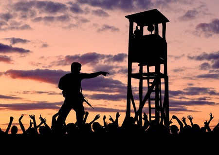 illegals: Concept of security. Silhouette of a military border guard on the background of the crowd of refugees and the watchtower