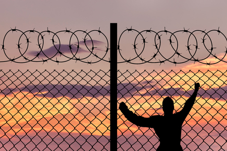 barbed wire fence: Concept of security. Silhouette of refugee men and metal fence with barbed wire on the background of the beautiful sky Stock Photo