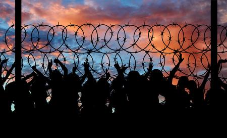 Concept van veiligheid. Silhouet van vluchtelingen klimmen over het prikkeldraad aan de grens