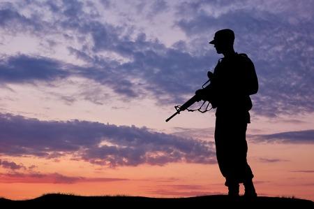silueta humana: Silueta del soldado con una pistola sobre un fondo de la puesta del sol Foto de archivo