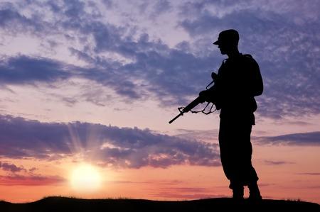 soldado: Silueta del soldado con una pistola sobre un fondo de la puesta del sol Foto de archivo