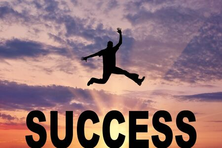 success man: Concept of success. Man jumping over the word success against the evening sky