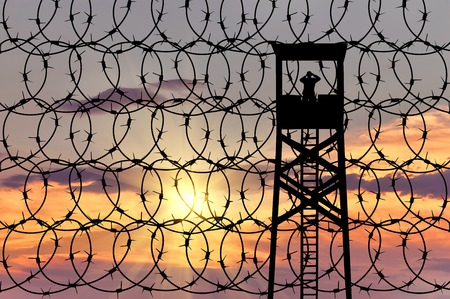 barbed wire fence: The concept of security. Silhouette of the observation tower on the background of the fence with barbed wire at sunset Stock Photo