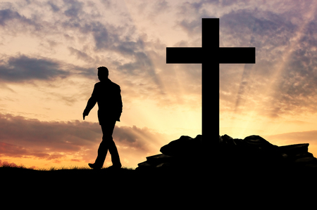 oncept: ?oncept of an atheist. Silhouette of a man on the background of the cross at sunset