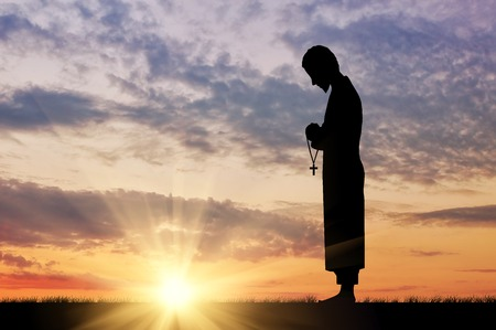 Concept of religion. Silhouette of a priest with a cross in his hand against the sunset