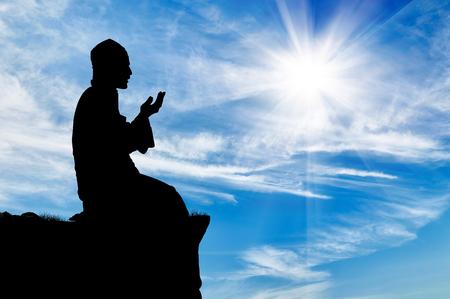 イスラムの宗教。背景の曇り空の上で祈っている人のシルエット