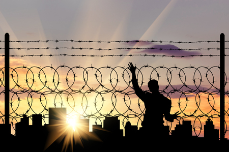 middle east crisis: Silhouette of a man near the refugee fence of barbed wire on the background of evening city