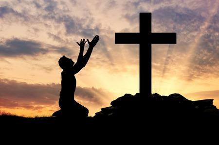 alabanza: concepto de religión. Silueta de un hombre rezando ante una cruz al atardecer