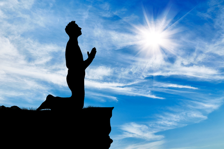 praise: Silhouette of man praying at the top against the beautiful cloudy sky Stock Photo