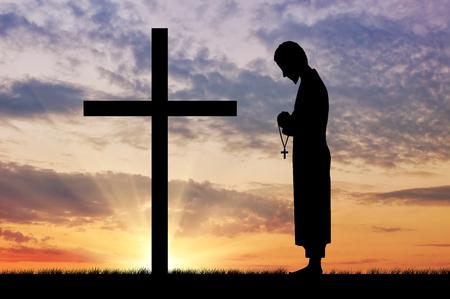 sacerdote: Concepto de la religi�n. Silueta de sacerdote y cruz sobre un fondo de cielo hermoso Foto de archivo