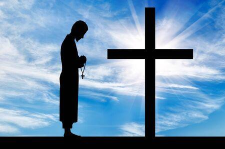 sotana: Concepto de la religión. Silueta de sacerdote y cruz sobre un fondo de cielo hermoso Foto de archivo