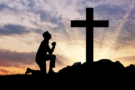 worship praise: concept of religion. Silhouette of a man praying before a cross at sunset