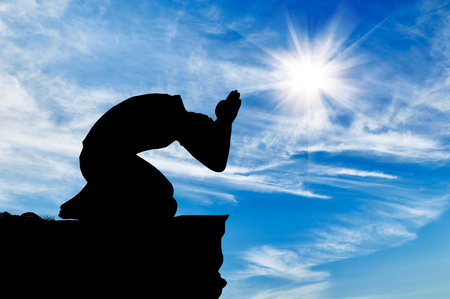 sun worship: Silhouette of man praying at the top against the beautiful cloudy sky Stock Photo