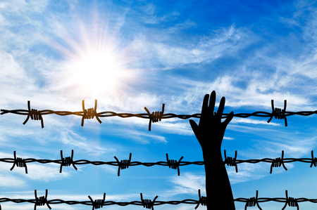 barbed wire fence: Concept of refugee. Silhouette helping hand to a refugee background fence of barbed wire Stock Photo