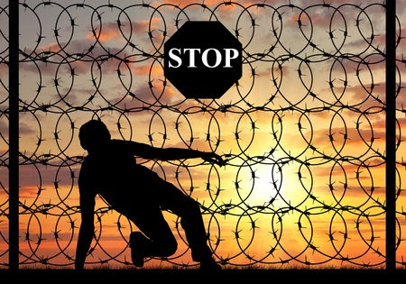 illegals: concept of the refugees. Silhouette of illegally crossing the border and refugee stop sign on a fence with barbed wire Stock Photo