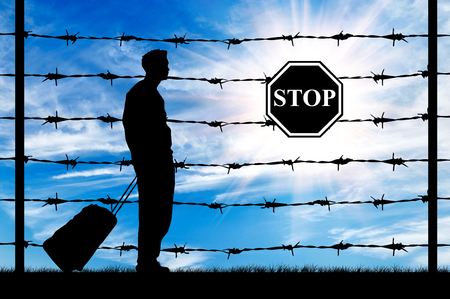 illegals: Concept of refugee. Silhouette of a refugee with a bag on a background of a fence with barbed wire and stop sign