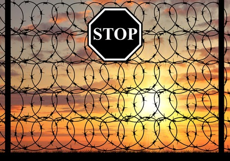 illegals: concept of refugee. Silhouette of fence with barbed wire and a stop sign at sunset Stock Photo