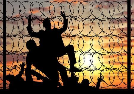 Concept van de vluchtelingen. Silhouet van illegaal oversteken van de grens vluchtelingen en stop teken op een hek met prikkeldraad Stockfoto