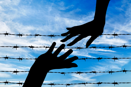 middle east war: Concept of refugee. Silhouette helping hand to refugees on the background of the fence of barbed wire Stock Photo
