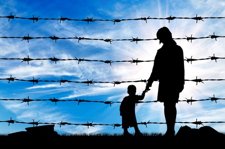 Concept of refugee. Silhouette of hungry refugees mother and child near the fence of barbed wire 스톡 콘텐츠