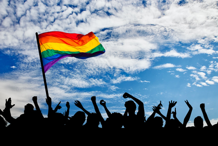 lesbian: Silhouette of a parade of gays and lesbians with a rainbow flag