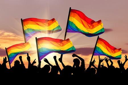 lesbienne: Silhouette d'un d�fil� des gays et lesbiennes avec un drapeau arc-en-au coucher du soleil Banque d'images