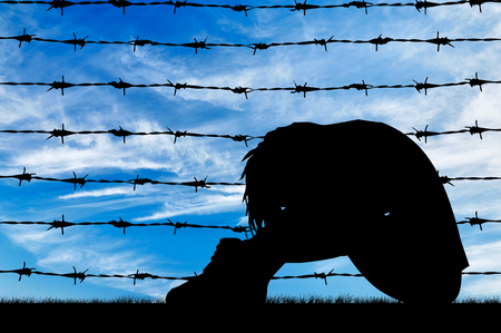 refugee: Concept of refugee. Silhouette Despair refugee woman near the fence of barbed wire