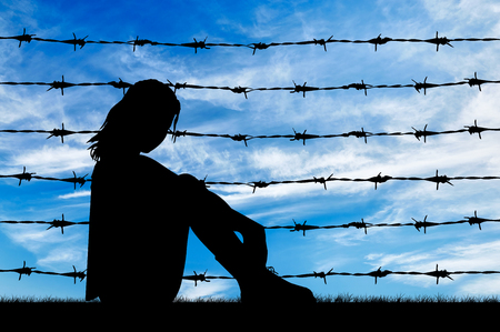 illegals: Concept of refugee. Silhouette Despair refugee woman near the fence of barbed wire