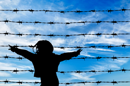 barbed wire fence: Concept of refugee. Silhouette of a refugee child near the fence of barbed wire Stock Photo