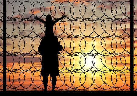 illegals: Concept of refugee. Silhouette of a family with a child refugee father near the fence with barbed wire at sunset