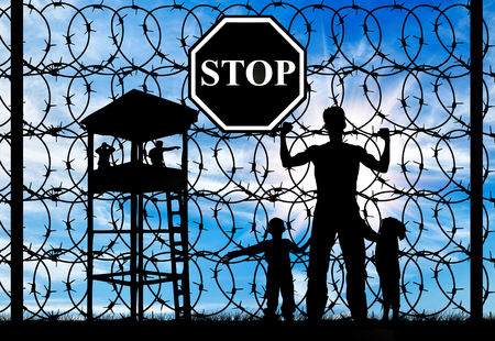 illegals: Concept of refugee. Silhouette of father and child refugees and fence with barbed wire and watch tower